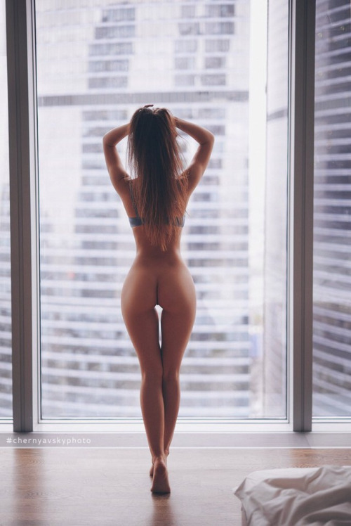 Slender naked girl at the window