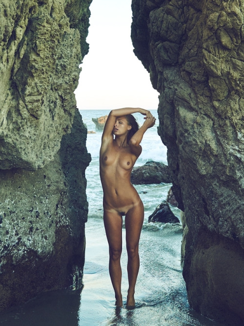 Slim nude girl posing at the rock
