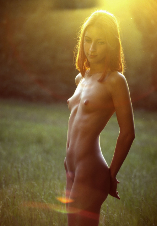 Slender naked girl in the rays of the sunset