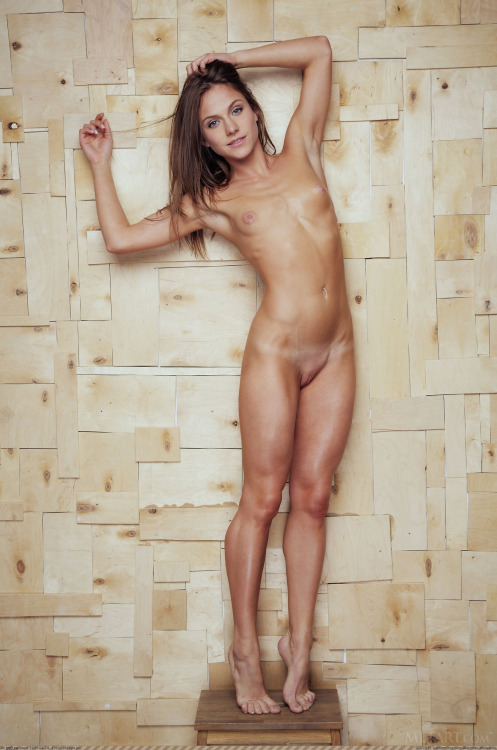 Thin naked girl posing on a stool