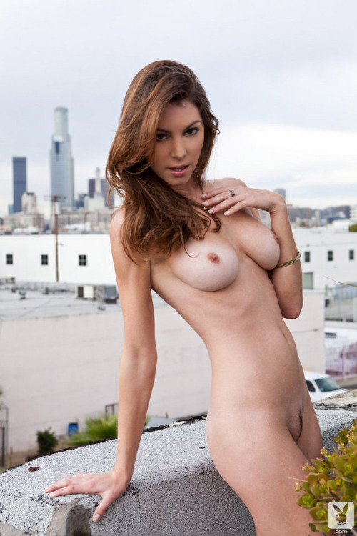 Slender naked girl at the urban landscape