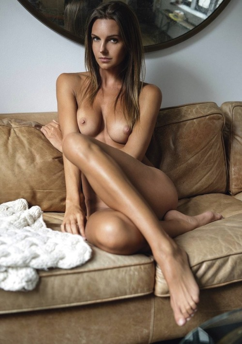 Sexy nude slender girl poses at the sofa
