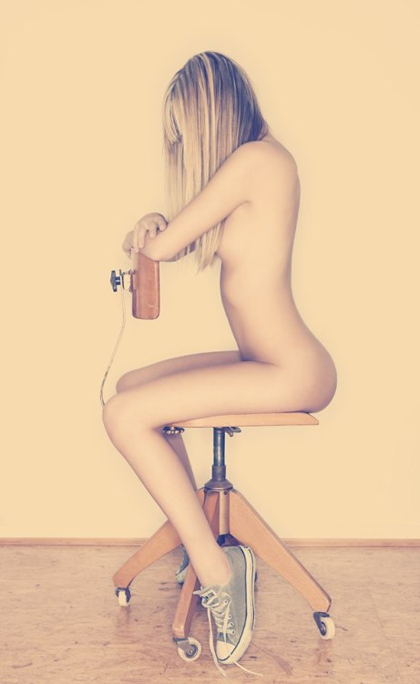 Gentle nude blonde girl poses on the chair