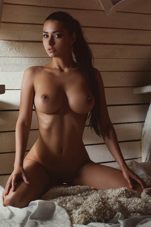 Cool tanned nude girl posing on the carpet