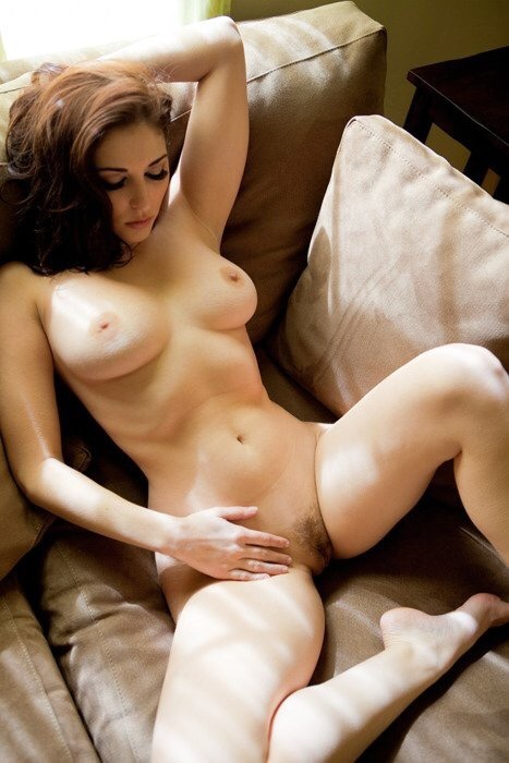 Nude girl is resting after a shift on the sofa from the sponsor