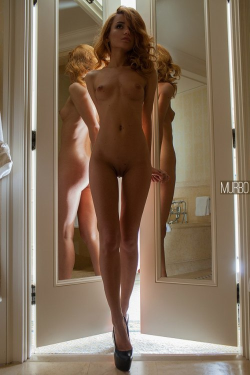Naked slim girl admires her reflection in the mirrors
