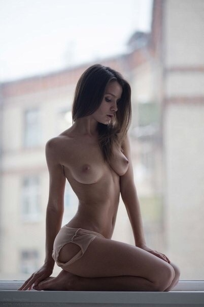 Sexy slender naked girl poses by the window