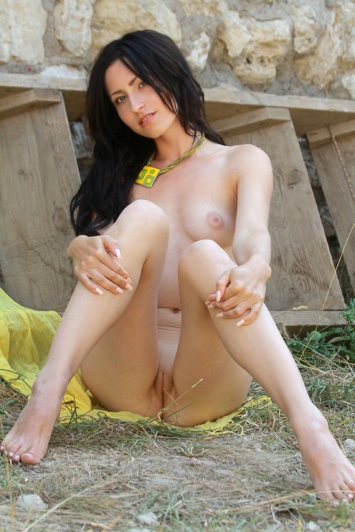 Showing pussy sitting on a wet grass