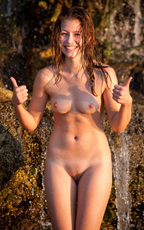 Nude smiling red-head girl under the waterfall