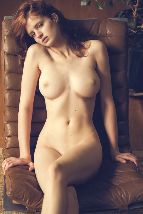 Nude red-head girl dreaming on the massive chair