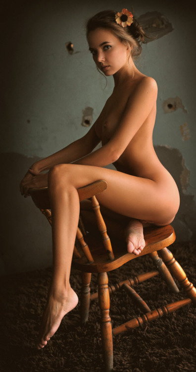 Beautiful skinny nude serious girl posing on a chair
