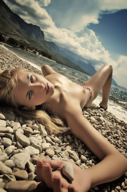 Naked skinny girl catches a sun on the stones