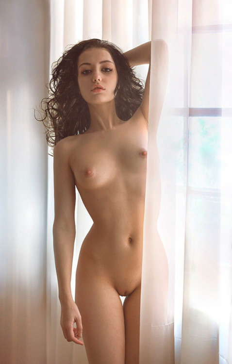 Melancholy nude slim skinny girl poses by the window