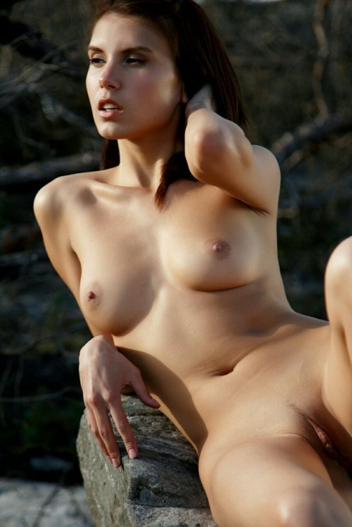 Nude brunette girl relaxes on the col stone