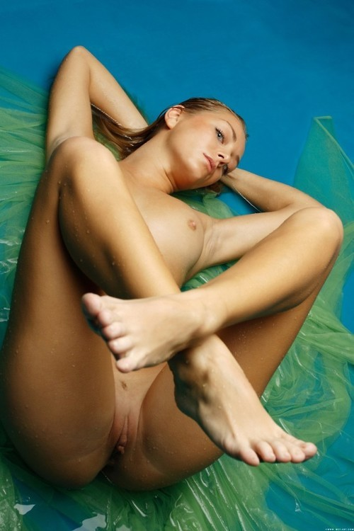 Crossing legs of nude girl on blue-green background