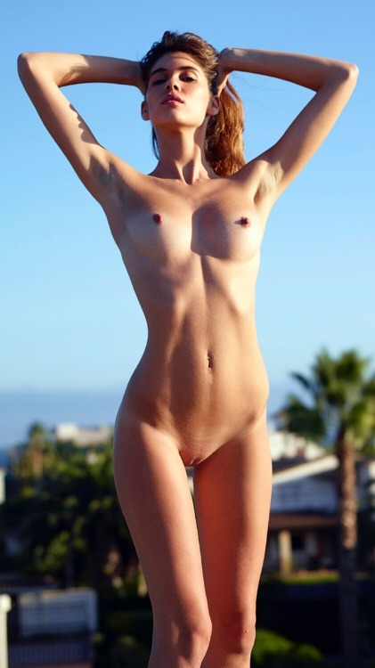 Naked girl looks elegant on a background of blue sky